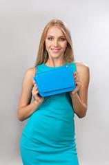 Блондинка с синей сумкой в руках
