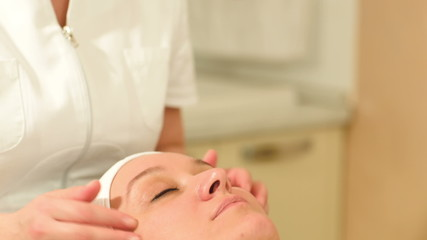 Therapist doing a facial massage at beauty spa