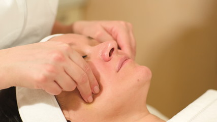 Seance of professional facial massage at beauty spa