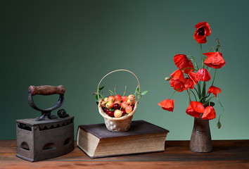 Red poppies in a ceramic vase, books, cherries and old flatiron