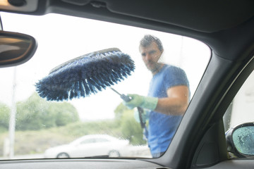 Man cleaning car glass with brush.