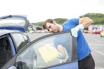 Man cleaning car glass with sponge.