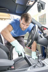 Man hoovering the car cabin, cleaning concept.
