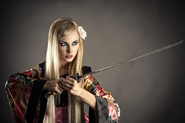 beautiful woman with samurai sword isolated on gray