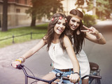 Portrait of funny boho girls on the tandem bicycle poster