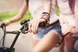 Close up of boho girls riding on bike poster