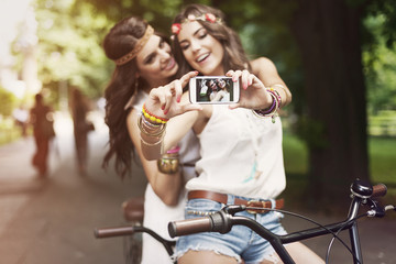 Hippie girls taking selfie at park