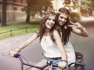 Portrait of funny boho girls on the tandem bicycle