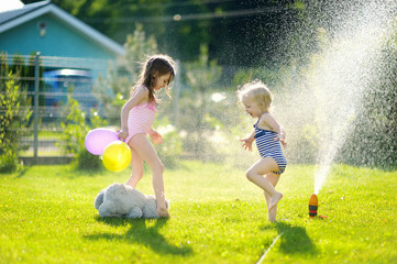 Girls running though a sprinkler in a backyard