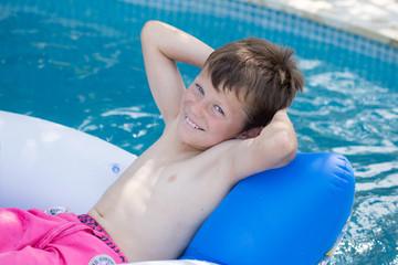 A la piscine : Enfant sur un fauteuil gonflable