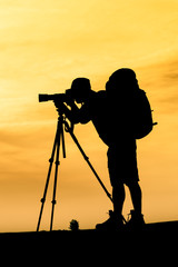 Silhouette of photographer shooting for a sunrise