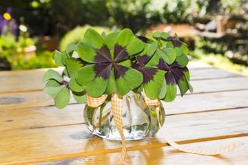 Kleeblätter als Blumenstrauß in Vase auf Holz