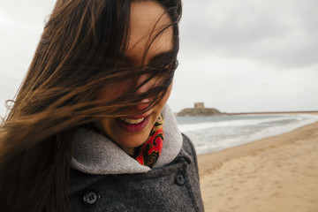 young woman on windy beach, Bosa, Sardinia, Italy