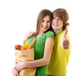 Portrait of a pretty young couple holding a grocery bag and smil