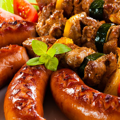 Grilled meat, sausages and vegetables on white background