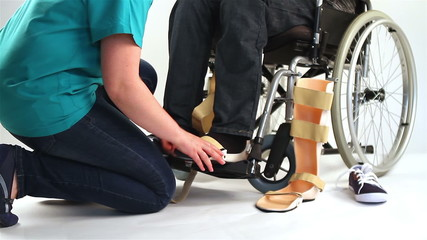 Orthopedist puts orthosis to patient with disabilities