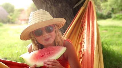 girl in hammock holding fresh watermelon slice