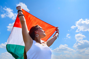 young beautiful cheerful woman holding italian flag against summ