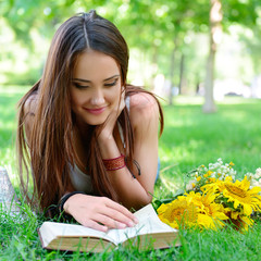 beautiful cheerful girl reading book in the summer park