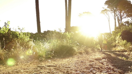 Young couple running together at sunrise in slow motion
