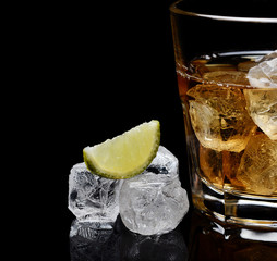 glass of whiskey with ice on a black background