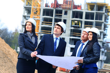 Portrait of builders standing at building site and discussing