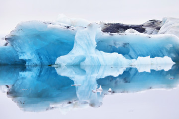 Blue iceberg symmetrically reflected in the water
