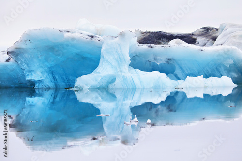 Foto op Canvas Gletsjers Blue iceberg symmetrically reflected in the water