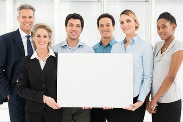 Smiling Teamwork Holding Blank Sign