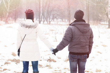 Young couple holding hands in the winter park
