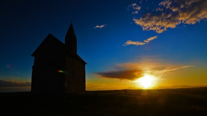 Time lapse sunset on hill with church