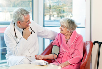 Doctor taking an elderly womans blood pressure.