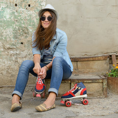 portrait of attractive happy girl with roller skates