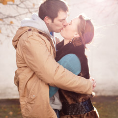 A young couple kisses in the autumn park