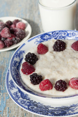 Breakfast porridge with frozen raspberries and blackberries.