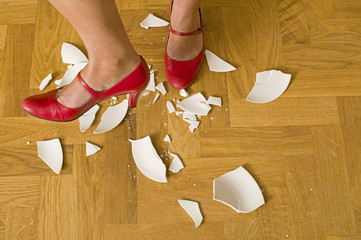 Angry woman stamping on smashed plates