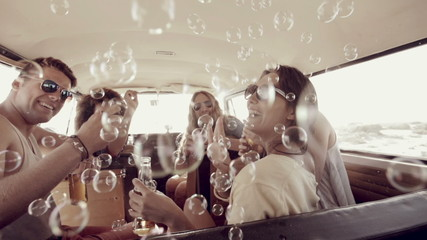 Hipsters blowing bubbles in camper van