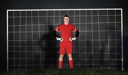Composite image of goalkeeper in red looking at camera