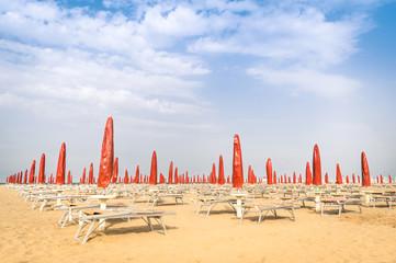 Red umbrellas and sunbeds at Rimini Beach - Italian summer