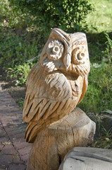 wooden carved owl in summer garden