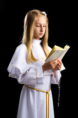 Girl reading Holy Bible for first communion