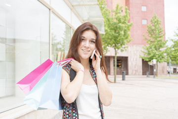 Smiling young woman with shopping bags talking by phone.