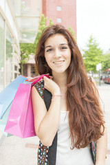 Smiling young woman with shopping bags in the street.