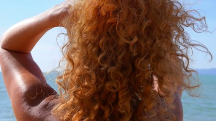 Woman Playing with Her Curly Red Hair on the Beach. Slow Motion.