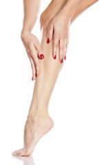pretty girl apply cosmetics on her leg