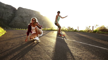 Friends longboard skating on road sunset
