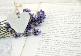 Weißes Herz und Lavendel auf alten Buchseiten