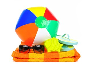 Beach ball, sunglasses and flip-flops on orange towel