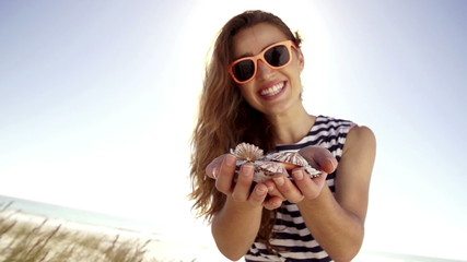 Teenage girl holding seashells on beach holiday