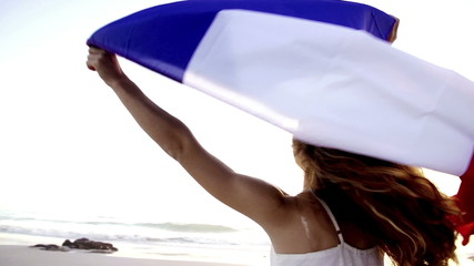 Girl spinning with french tricolore flag in slow motion